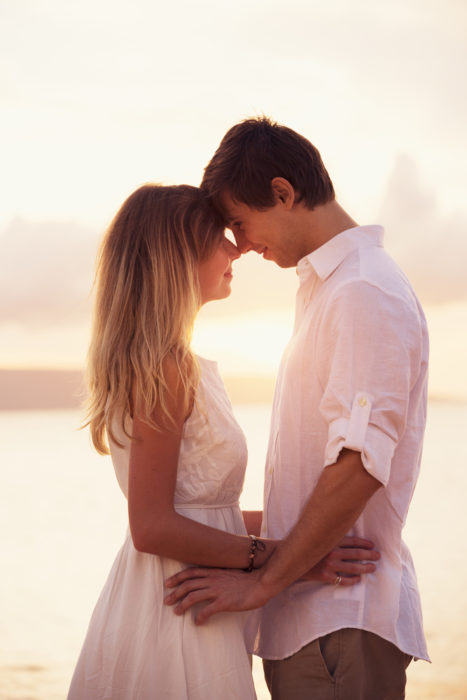 Romantic couple in love on the beach at sunset