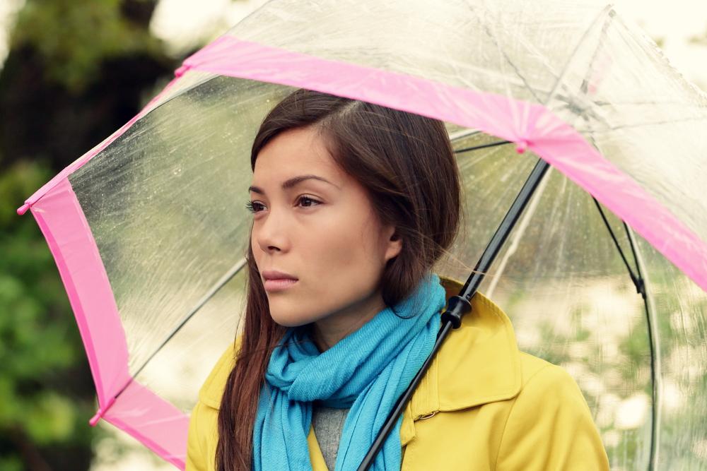 asian woman holding umbrella in rain