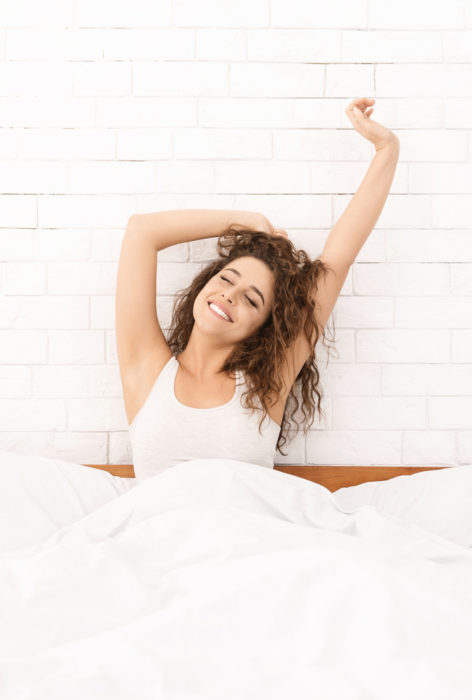 Comfortable mattress. Happy rested woman stretching in morning, enjoying her new bed, closeup